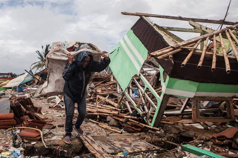 Un hombre rescata pertenencias entre los escombros en Labuan (Indonesia).