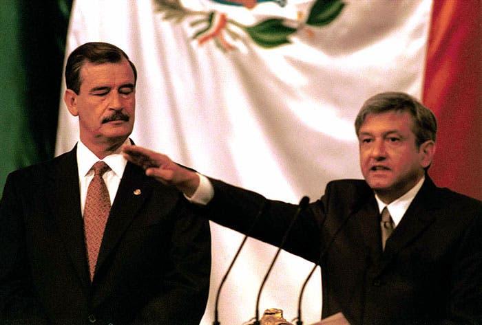 """Andrés Manuel López Obrador, en el momento de rendir protesta como Jefe de Gobierno del Distrito Federal en el 2000, se nota la """"alegría"""" de Fox. Foto. Cuartoscuro."""