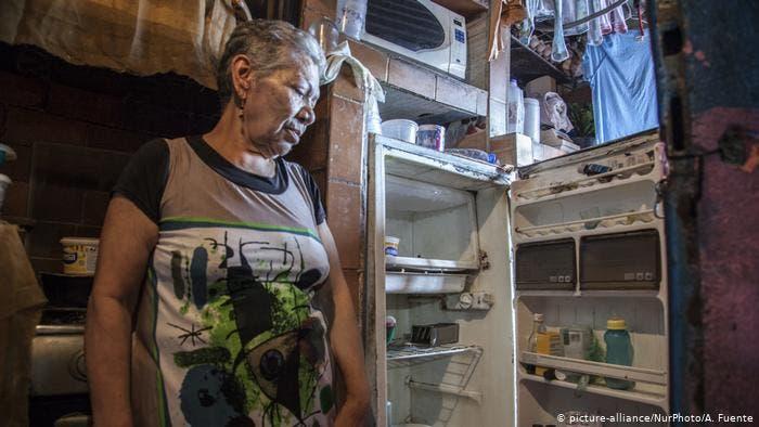 Con tristeza la señora de la casa observa su refrigerador, casi vacío.