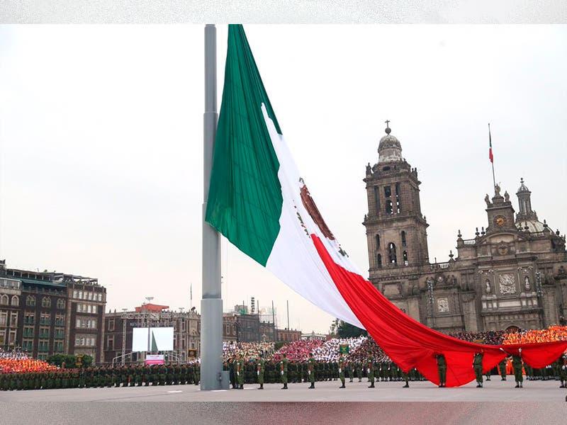 Civiles ayudan a militares a bajar bandera del Zócalo en fuerte lluvia