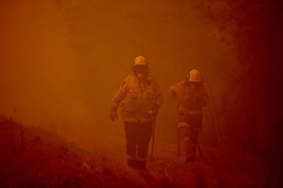 Bomberos aplacan un incendio entre el denso humo en la ciudad de Moruya, al sur de la Bahía de Batemans, en Nueva Gales del Sur, el 4 de enero del 2020. Peter Parks / AFP