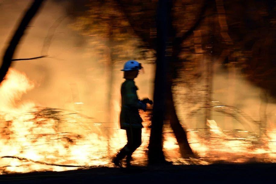 Imagen del 7 de diciembre de 2019, muestra a unos bomberos llevando a cabo una quema controlada para asegurar que las llamas no se extendieran hasta zonas residenciales de Mangrove, a 100 kilómetros al norte de Sídney. Saeed Khan / AFP