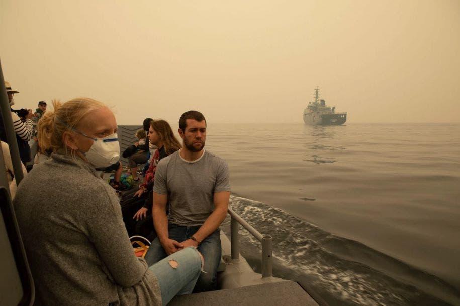 Imagen tomada el 3 de enero de 2020 y publicada por la Armada Real Australiana, se ve a gente evacuada de Mallacoota, un estado de Victoria, en una lancha de desembarco que se dirige al navío MV Sycamore. Shane Cameron / Armada Real Australiana / AFP