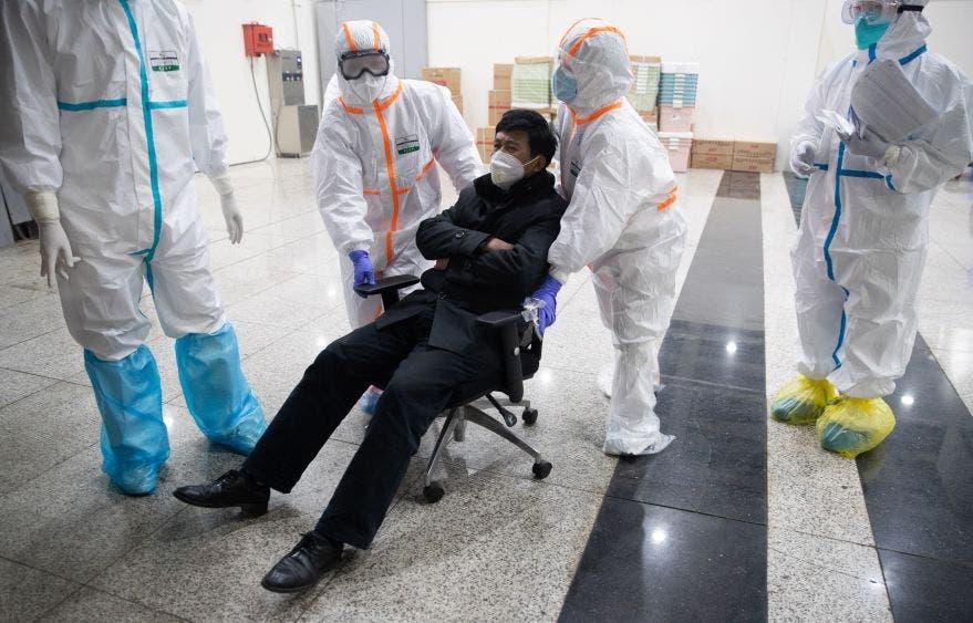Personal médico del Hospital en Wuhan contra el coronavirus, lleva a una persona infectada en una silla rodante que hace las veces de camilla.