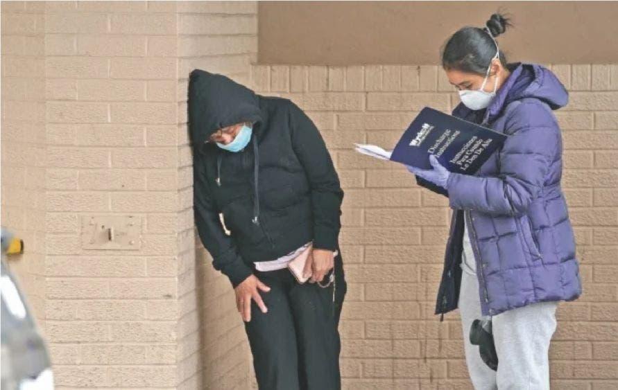 Una mujer angustiada se apoya contra una pared afuera del Hospital Wyckoff, en Nueva York.