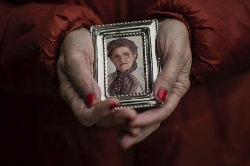 Teresa Navarro muestra una fotografía de su madre, Concepción Rosinos, de 97 años, en Madrid, España.