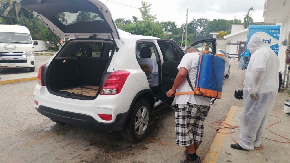 Taxistas desinfectan vehículos particulares para contener el Covid-19.