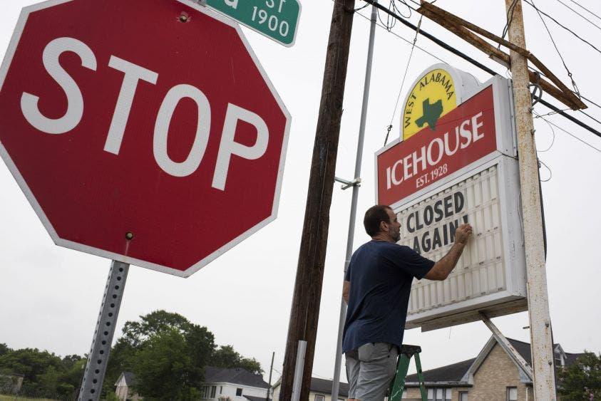 """Un trabajador restaurantero de Alabama, Estados Unidos, coloca un letrero de """"otra vez cierre por Covid-19""""."""