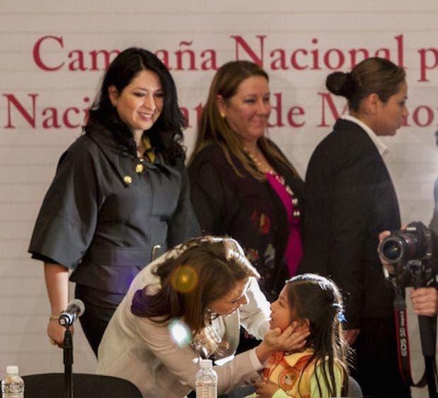 Laura Iberia Vargas Carrillo -esposa de Miguel Ángel Osorio Chong- primera a la izquierda de pie, junto a Angélica Rivera Hurtado, quien se agacha para acariciar a una niña, tiempos de simulación.