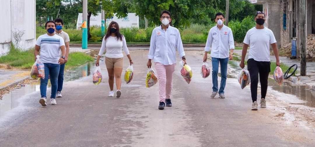 Jóvenes políticos reparten comida chatarra en Chetumal.