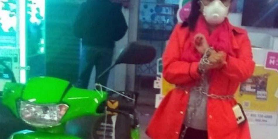 Mujer se encadena a motocicleta para que se la vendan a 14 pesos