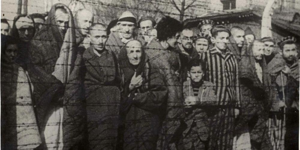 Sobrevivientes del Holocausto se paran detrás de una cerca de alambre de púas después de la liberación del campo de exterminio alemán nazi Auschwitz-Birkenau en 1945. /Reuters