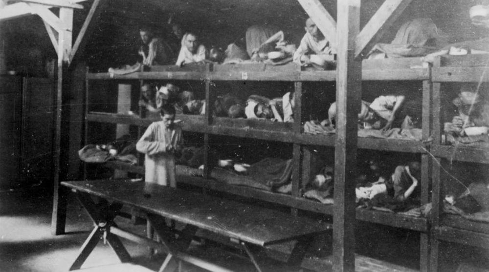 Personas acostadas en literas en una barraca en el campo de exterminio alemán nazi Auschwitz-Birkenau después de su liberación en 1945. / REUTERS