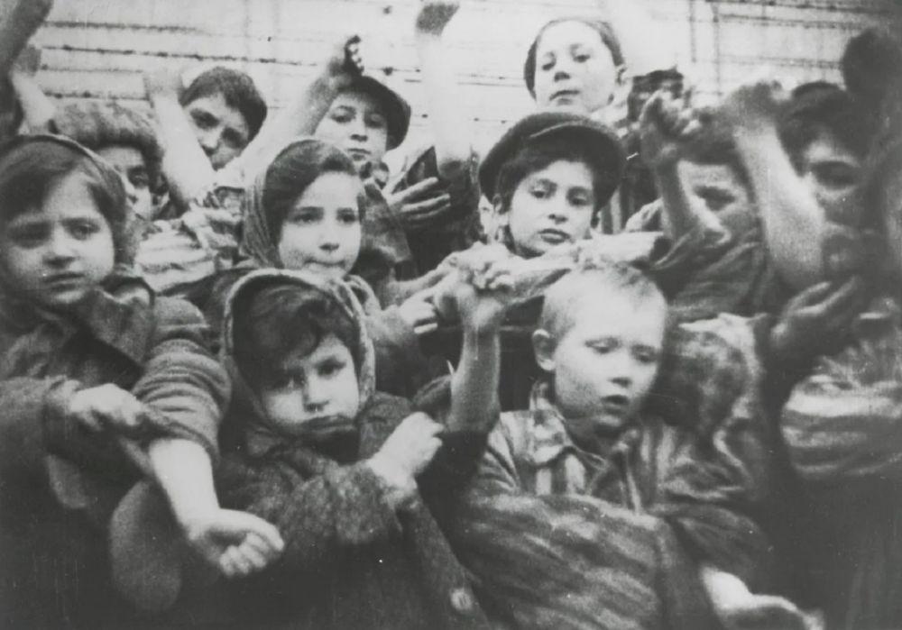 Niños en el campo de concentración de Auschwitz-Birkenau en Oswiecim mostrando sus números tatuados en sus brazos. /Museo y Memorial de Auschwitz /EFE