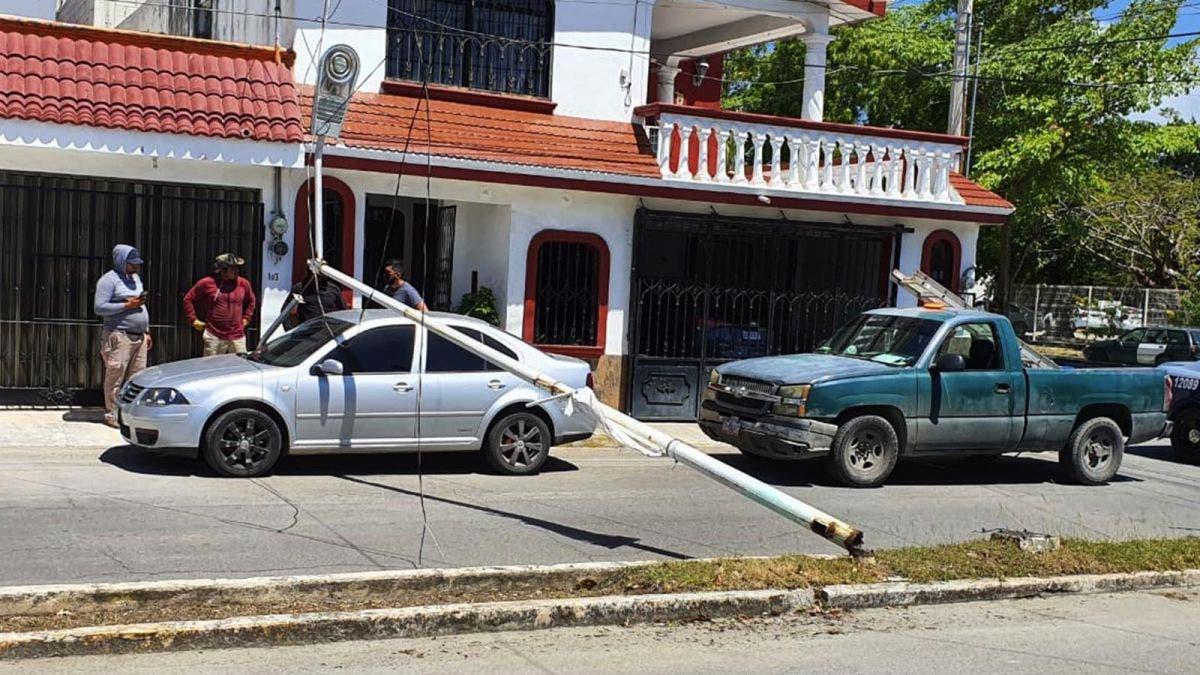 Poste del alumbrado público cae encima de automóvil